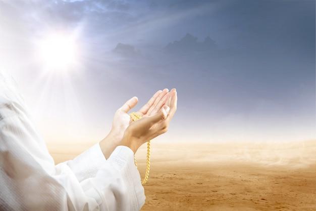 Homme musulman priant avec des perles de prière sur ses mains dans le désert