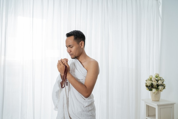 Homme musulman priant en vêtements traditionnels blancs