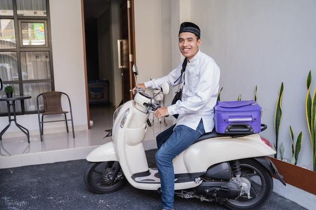Homme musulman voyageant pour eid mubarak lebaran en moto