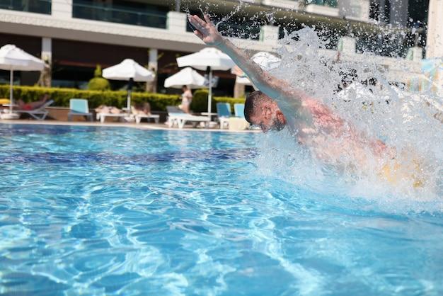 L'homme nage avec un coup de sein dans une piscine bleue d'eau claire.