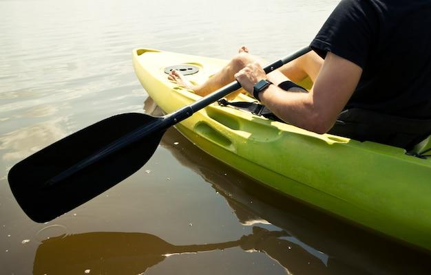 L'homme nage sur un kayak sur le lac