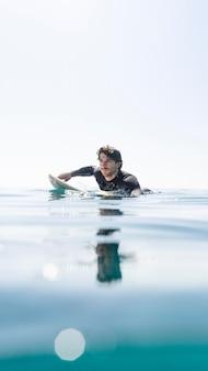 Homme nageant sur une planche de surf