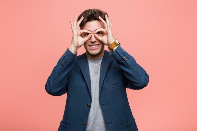 Homme naturel jeune entreprise montrant un signe correct sur les yeux