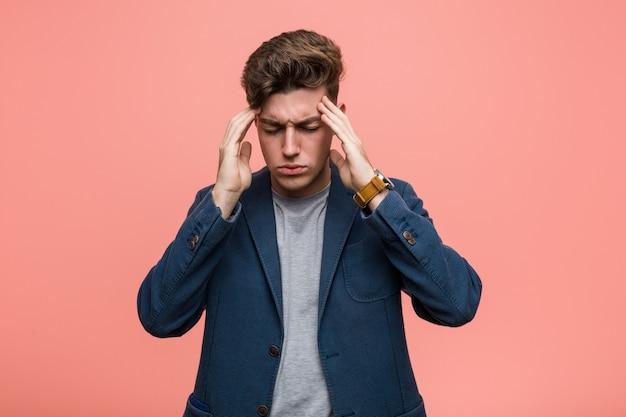 Homme naturel jeune entreprise touchant les tempes et ayant des maux de tête.
