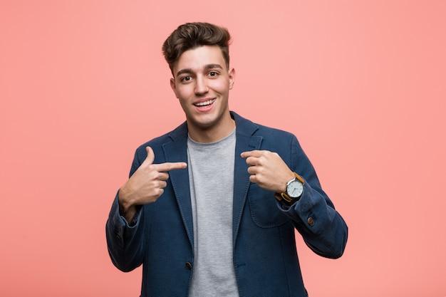 Homme naturel de jeunes entrepreneurs surpris en se pointant, souriant largement.