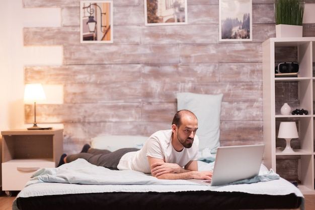 Homme naviguant sur un ordinateur portable la nuit au lit en pyjama.