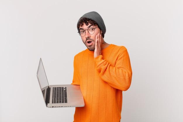 Homme nerd avec ordinateur se sentant choqué et effrayé, l'air terrifié avec la bouche ouverte et les mains sur les joues