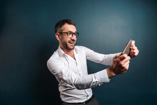L'homme nerveux joue à des jeux par téléphone mobile.