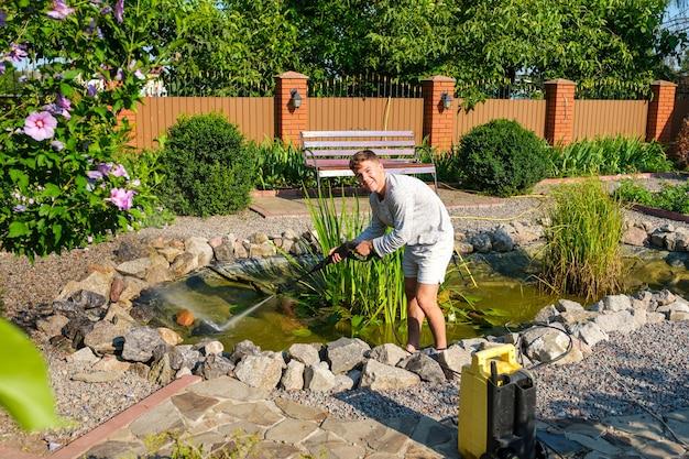 L'homme nettoie le fond de l'étang du jardin avec un nettoyeur haute pression de la boue et des boues