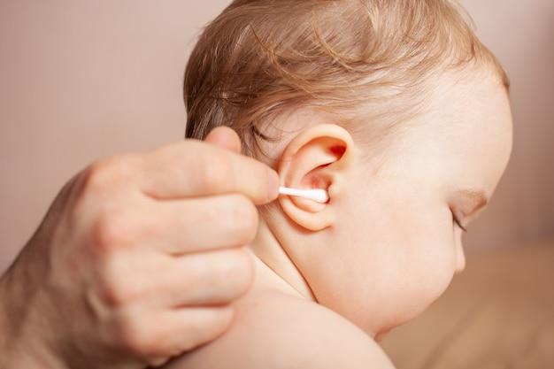 Un homme nettoie les oreilles de son enfant