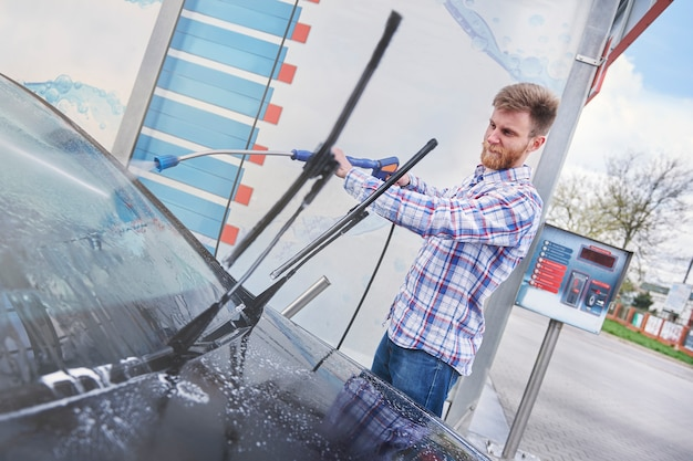 L'homme nettoie sa voiture dans un self-service