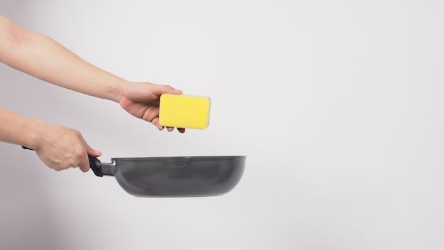 Homme de nettoyage de casserole main sur fond blanc nettoyer la casserole antiadhésive avec une éponge à vaisselle pratique