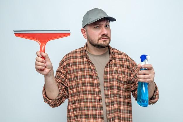Homme de nettoyage impressionné tenant une raclette et un nettoyant en aérosol