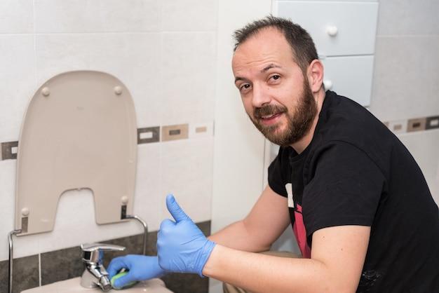 Homme nettoyant la cuvette des toilettes. émotion positive montrant les pouces vers le haut.