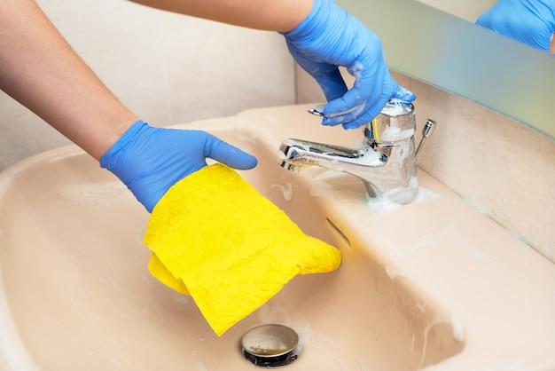 Homme nettoyant le lavabo de la salle de bain