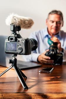 Homme nettoyant l'objectif de son appareil photo avec un souffleur d'air en caoutchouc