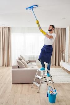 Homme nettoyant le plafond et les lampes dans le salon. concept de service de nettoyage de maison.