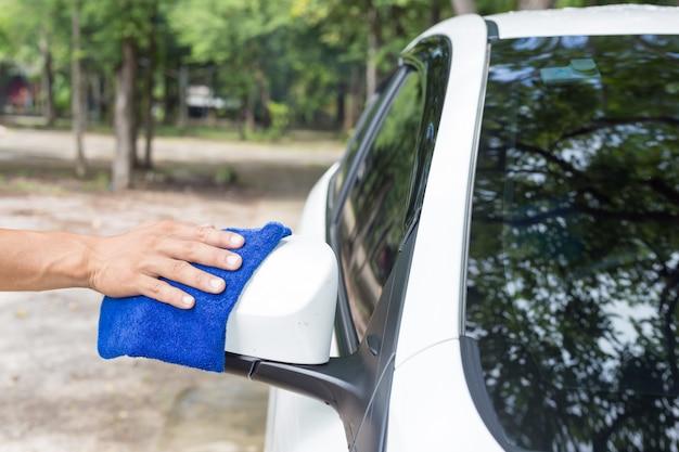 Homme nettoyant une voiture avec un chiffon en microfibre - concepts de voiture détaillant et valeting