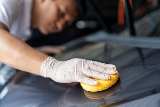 L'homme de nettoyer l'extérieur de la voiture à l'aide d'une éponge