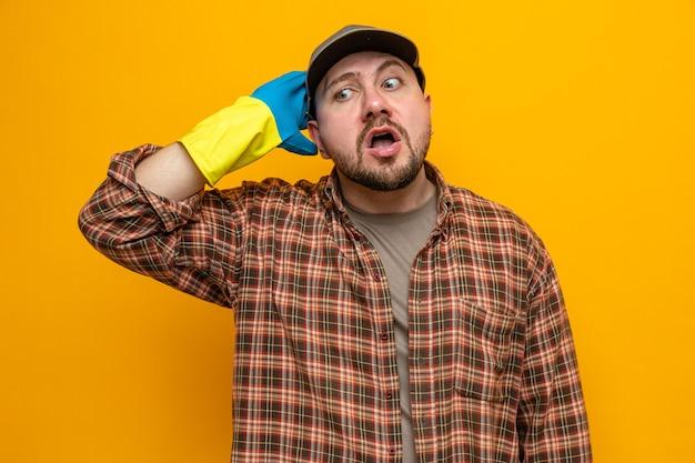 Homme nettoyeur slave anxieux avec des gants en caoutchouc mettant la main sur sa tête et regardant de côté