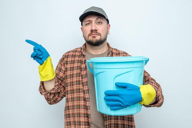 Homme nettoyeur slave confiant avec des gants en caoutchouc tenant un seau et pointant sur le côté