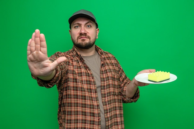 Homme nettoyeur slave confiant tenant une éponge sur une assiette et gesticulant un panneau d'arrêt