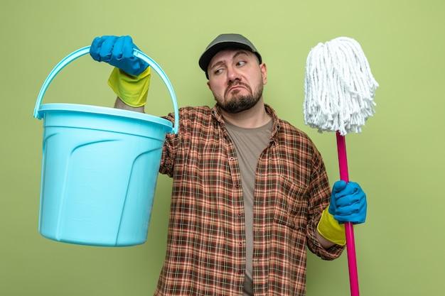 Homme nettoyeur slave confus avec des gants en caoutchouc tenant un seau et une vadrouille