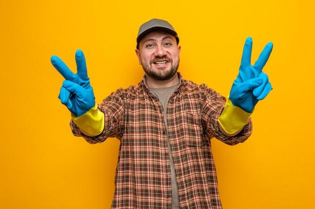 Homme nettoyeur slave souriant avec des gants en caoutchouc gesticulant le signe de la victoire