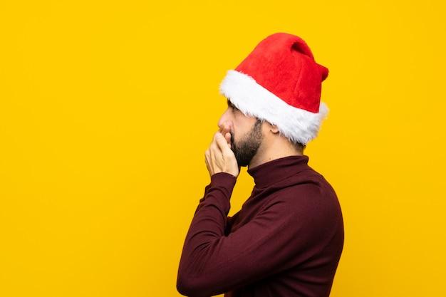 Homme, à, noël chapeau, sur, isolé, mur jaune, couvrir bouche, et, regarder, côté