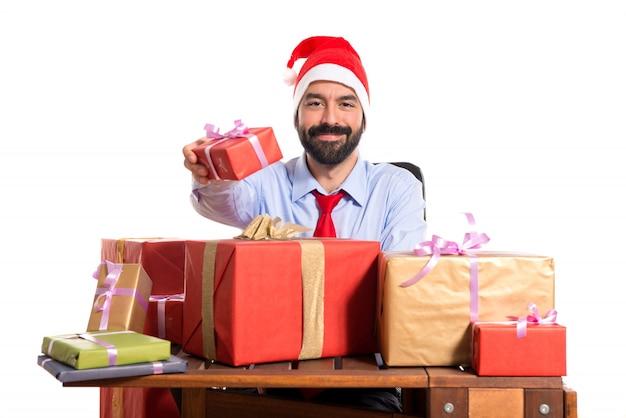 Homme de noël dans son bureau avec plusieurs cadeaux