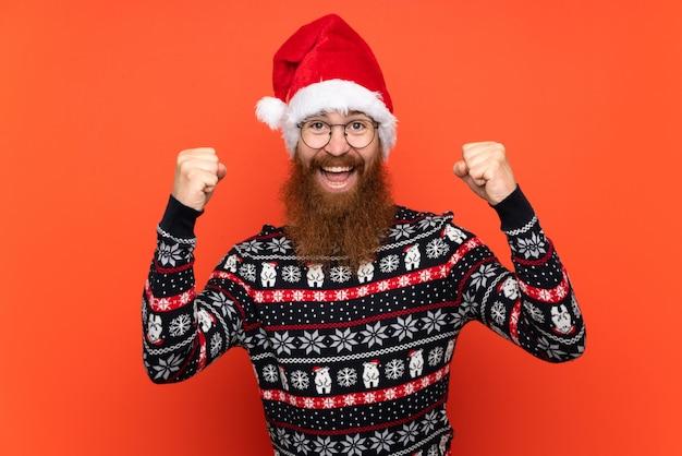 Homme de noël avec une longue barbe sur un mur rouge isolé célébrant une victoire