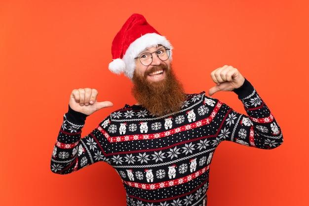 Homme de noël avec une longue barbe sur un mur rouge isolé fier et satisfait