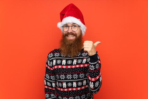 Homme de noël avec une longue barbe sur un mur rouge isolé avec le pouce levé