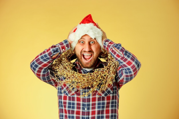 Homme de noël souriant portant un bonnet de noel sur le studio orange