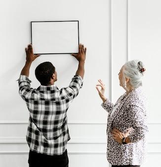 Homme noir accrochant le cadre d'art floral sur le mur