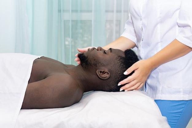 Un homme noir adulte reçoit un massage du visage et de la tête d'une masseuse en cabinet privé