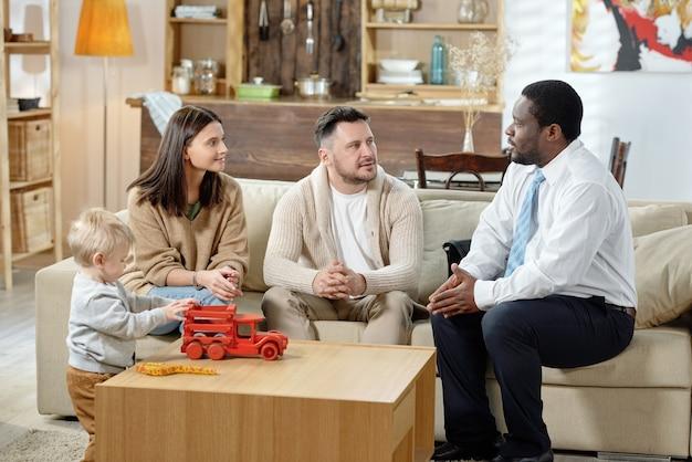 Homme noir adulte visitant la jeune famille avec enfant et consultation sur le prêt immobilier