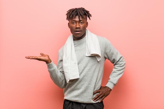 Homme noir africain de fitness jeunes montrant un espace de copie sur une paume et tenant une autre main sur la taille.