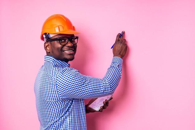 Un homme noir afro-américain écrit des idées dans un cahier peint le mur de couleur rose. un constructeur africain heureux à l'intérieur de la maison, un homme d'affaires porte un casque de protection. étudiant en chef jeune homme
