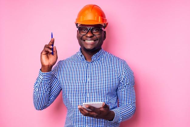 Un homme noir afro-américain écrivant des idées dans un cahier peint le mur de couleur rose. une maison de constructeur africaine heureuse, un homme d'affaires architecte designer porte un casque de protection. jeune étudiant en chef.