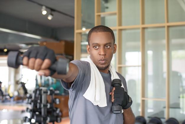 Homme noir concentré tenant des haltères et la boxe