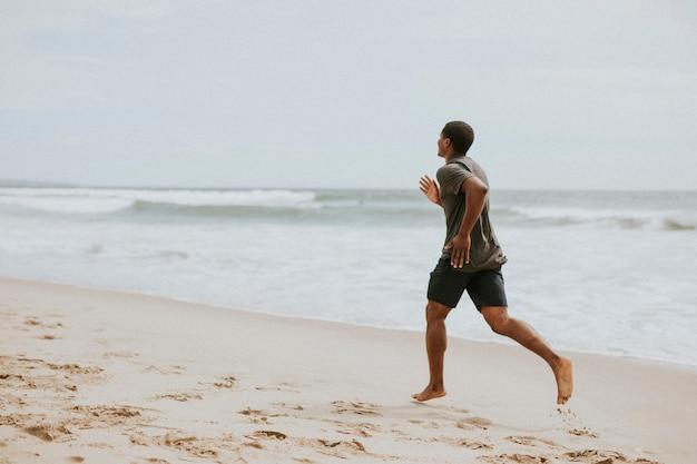 Homme noir courant sur la plage