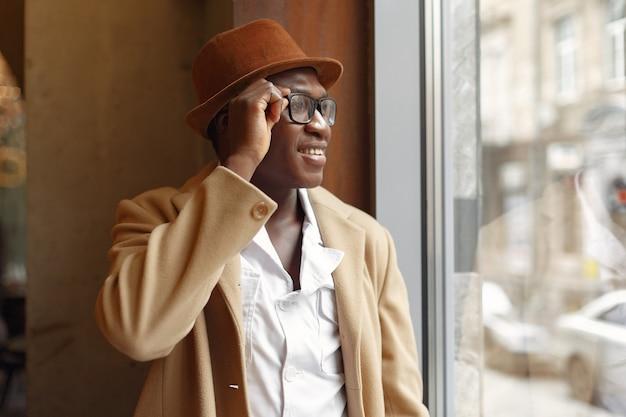 Homme noir dans un manteau brun debout près de la fenêtre
