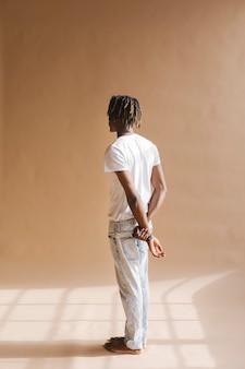 Homme noir debout près d'un fond beige