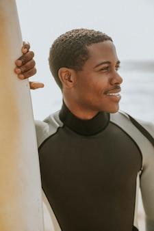 Homme noir debout près de la planche de surf