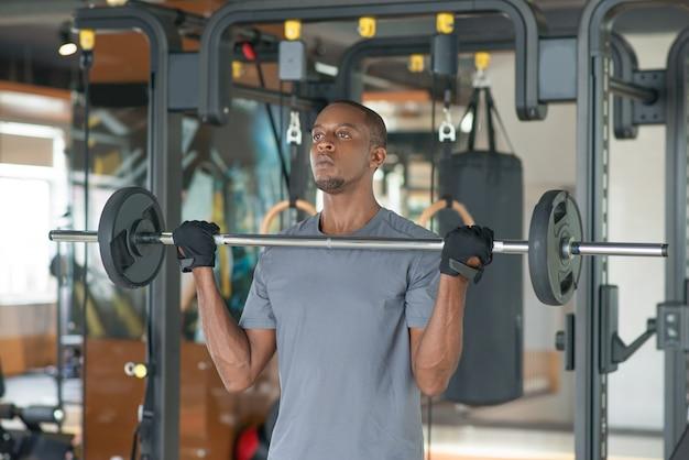 Homme noir debout et soulever une barre dans la salle de gym