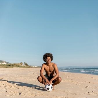 Homme noir décontracté avec ballon sur la plage