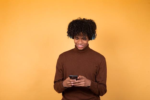 Homme noir écrivant des messages à quelqu'un, portant des vêtements décontractés, souriant isolé en studio sur fond jaune.