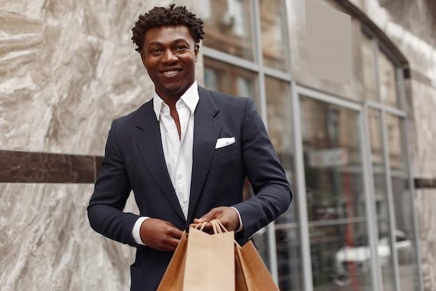 Homme noir élégant dans une ville avec des sacs à provisions