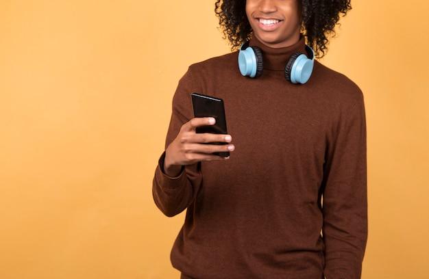 Homme noir envoyant des sms à quelqu'un, portant des vêtements décontractés, souriant isolé en studio avec espace copie